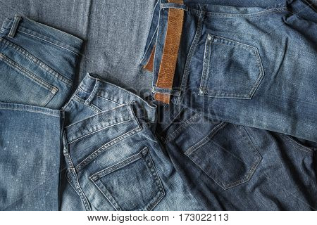 Top View Of New Jeans And Faded Jeans On Blue Fabric Background