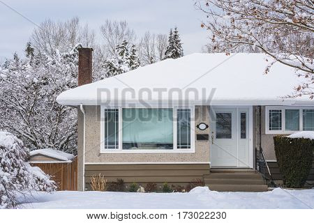 Entrance of family house with front yard in snow. Residential house on winter cloudy day