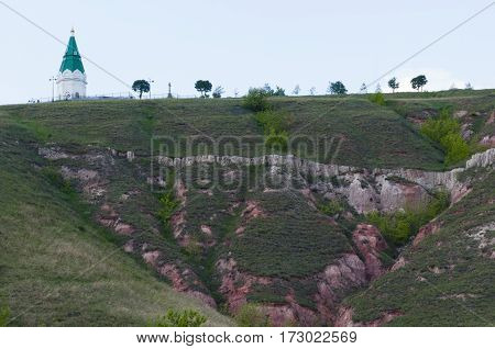 unusual mountain landscape with a small chapel and a bell at mountain top