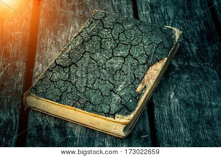 Old tattered book on a wooden table. Reading by candlelight. Vintage composition. Ancient library. Antique literature. Fabulous atmosphere. Medieval and mystical background vintage style religion.