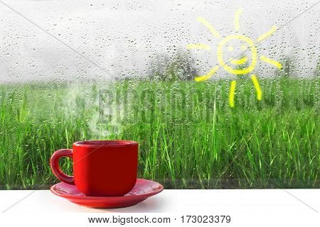 Red Cup of hot coffee on the table. The view from the window on nature. Wet fog on the window after rain. Drops of rain strike the glass. The comfort and warmth of the hearth. Rain outside the window.