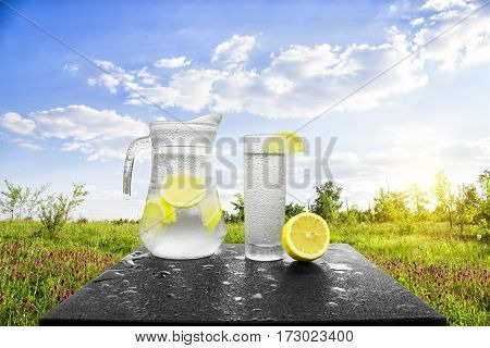 Fresh cold water with lemon and ice in a pitcher on the table.Homemade lemonade with fresh citruses on the background of nature. Quenching thirst.The condensation on the jug and a glass of cold water.