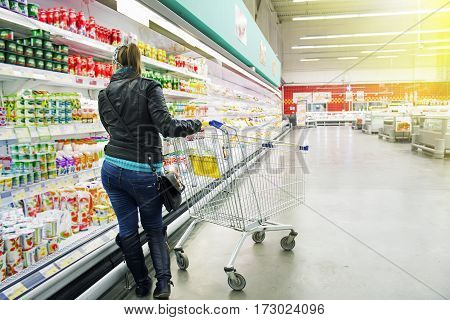 Cart at the Grocery Store. Girl holding a cart and chooses products.