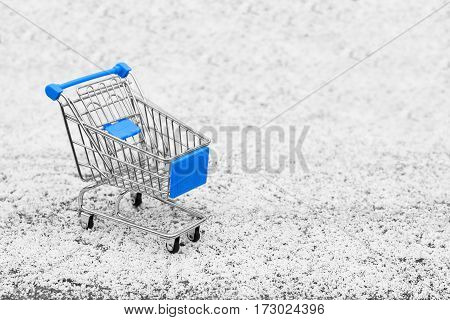 Cart from the grocery store on the snow. Concept winter shopping. New Year and Christmas buying. Retail trade and advertising. Business ideas. Purchase in the store. Empty shopping cart.