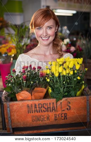 Female florist holding crate of flower bouquet in the flower shop