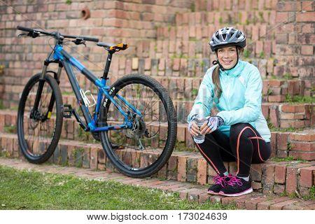 Portrait of beautiful female biker relaxing in countryside