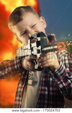 Little boy in shirt with a black gun, boy posing, the man takes aim ,