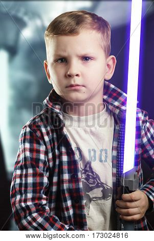 Little boy posing with a laser sword , a blue bright light, a young boy with a serious face, an aspiring actor,