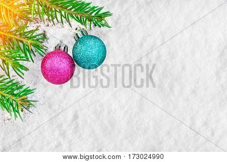 Christmas tree and decorations on the snow surface. Picturesque winter composition. Holiday mood. Xmas and New Year fairy tale background with sparkling bokeh lights. Beautiful greeting card.