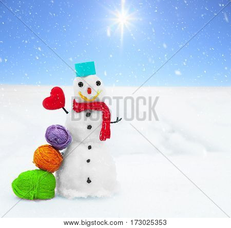 Smiling snowman and Christmas decorations in the forest during a snowfall. Picturesque winter landscape. Holiday mood. Xmas and New Year fairy tale background. Beautiful greeting card. Magic nature.