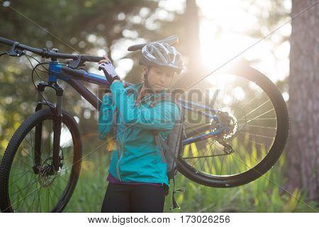 Female biker carrying mountain bike in countryside
