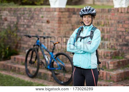 Portrait of beautiful female biker standing with arms crossed in countryside