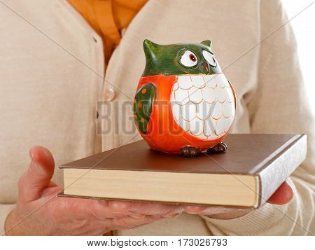 Close up picture of an elderly woman holding a book and an owl as the symbol of wisdom