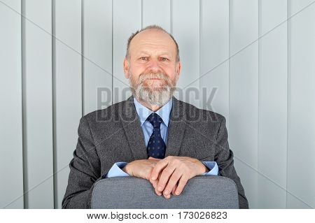 Picture of an aged elegant man standing at the office