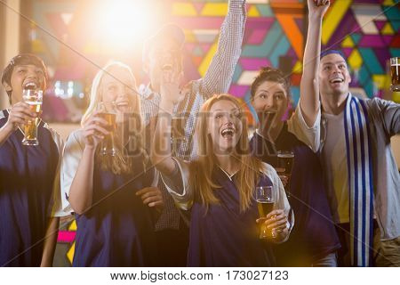 Group of friends cheering in party while having glass of champagne at bar