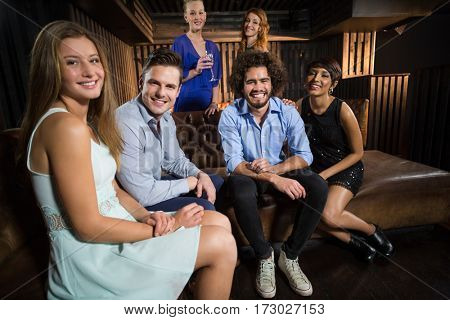 Portrait of smiling friends sitting together in sofa at bar