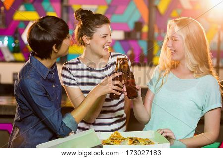 Three smiling female friends toasting bottle of beer in party at bar