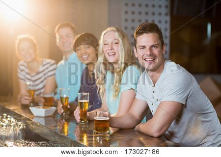 Portrait of smiling friends having glass of beer at counter in bar