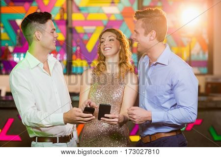 Smiling friend interacting with each other while using mobile phone in bar