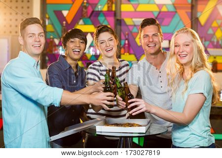 Portrait of smiling friends toasting bottle of beer in party at bar