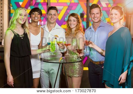 Portrait of smiling friends holding glass of cocktail in bar