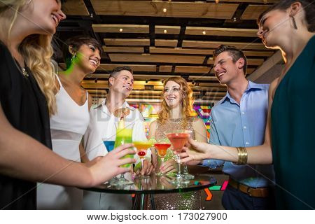 Group of friends interacting with each other while having cocktail in bar