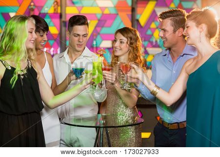 Group of smiling friends toasting glass of cocktail in bar