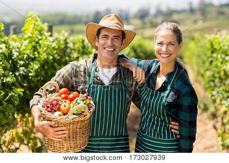 Portrait of happy farmer couple holding a basket of vegetables in the vineyard