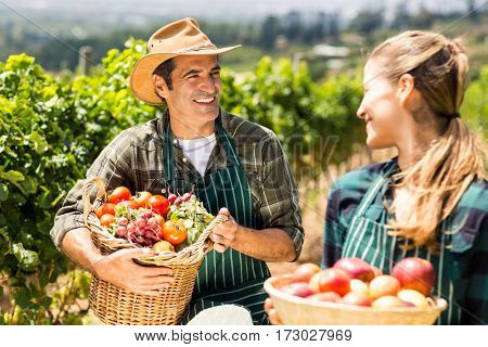 Happy farmer couple holding baskets of vegetables and fruits in the vineyard