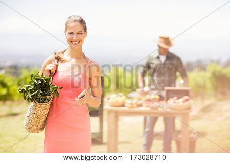 Portrait of female customer standing in front of vegetable stall at local market