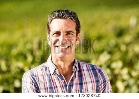 Portrait of smiling male vintner standing in vineyard