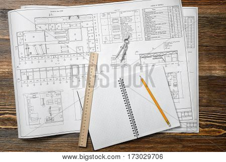 Open blueprints on wooden table background with a pencil, a ruler and compasses lying beside. Engineering and design. Construction projects. Planning.