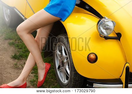 Naked and sexy legs of a girl sitting on a retro yellow car in summer..