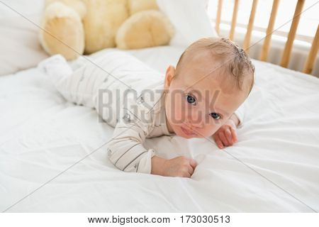 Baby lying on baby bed at home