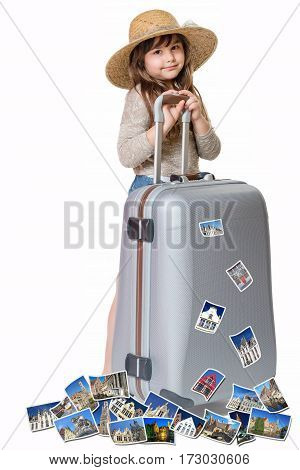 Long haired little girl with straw hat is standing and leaning on a suitcase. Photos of the sights of Bruges flies around the suitcase. All is on the white background. Vertically.