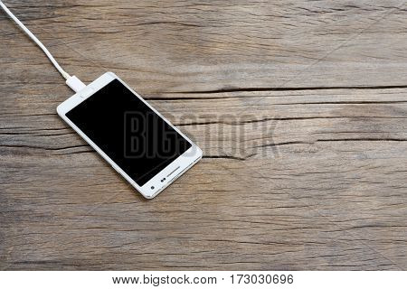 Smart phone and USB charger on wooden background