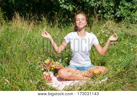 Young woman meditating in lotus position while doing yoga in a wonderful forest. Travel, Healthy Lifestyle concept.