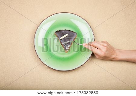 Hand With Fork Ready To Take Piece Of Chocolate Cake On Green Dis