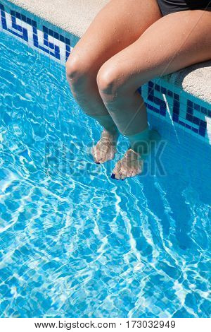 detail of legs of woman sitting on curb of pool feet in water nails painted blue and black swimwear