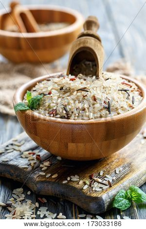 Wooden Scoop In A Bowl With A Mixture Of Four Types Of Rice.