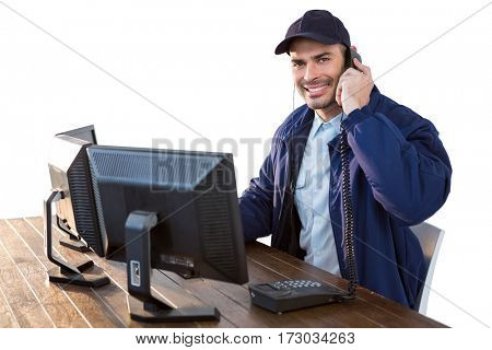Happy Security officer talking on the phone while using computer against white background