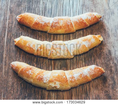 three croissant on wooden background top view