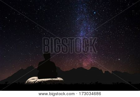 Silhouette a man sitting relaxing under the sky with milky way and stars at night