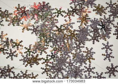 Close-up of snowflake christmas decoration scattered on wooden table