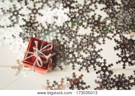 Close-up of small wrapped gift box and snowflake scattered on wooden table