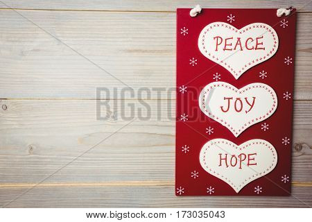 Christmas label with massages of peace, joy and hope on wooden table