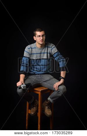 Young man standing on a chair and holding old camera on dark background