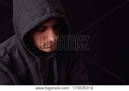 Confident And Serious Young Man Wearing Black Hoodie On A Black Background. Studio Shot.