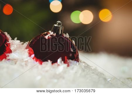 Close-up of christmas baubles on snow during christmas time
