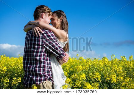 Romantic couple embracing each other in mustard field on a sunny day